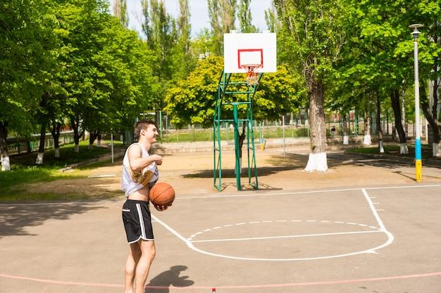 무성한 녹색 공원에서 코트에서 혼자 농구를 하는 젊은 운동 남자