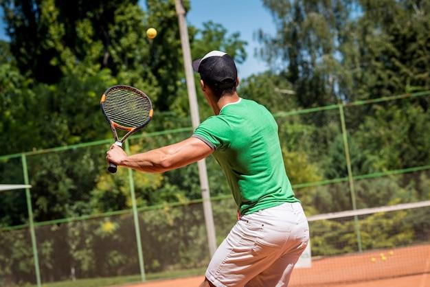 Молодой спортивный человек играет в теннис на корте.