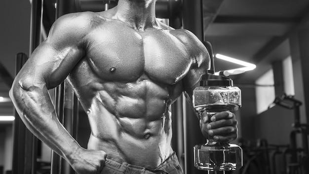 トレーニングでジムで筋肉をポンピングする若い運動選手スポーツとヘルスケアの概念の背景