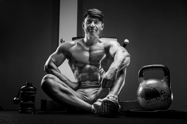 トレーニングスポーツとヘルスケアの概念でジムで筋肉をポンプでくむ若い運動男