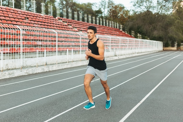 Young athletic man running on the stadium in the morning