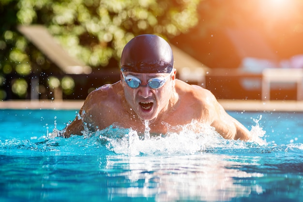 Young athletic man swimming in the swimming pool