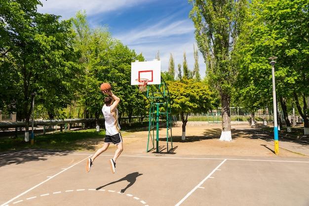 무성 한 녹색 공원에서 농구 코트에 키에서 점프 슛을 복용 하는 젊은 운동 남자