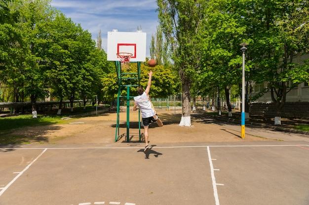 무성 한 녹색 공원에서 농구 코트에 바구니에 레이 업 샷을 복용 하는 젊은 운동 남자