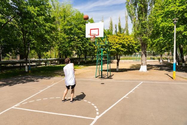 무성한 녹색 공원의 농구 코트에서 키 위에서 바구니에 총을 쏘는 젊은 운동 남자