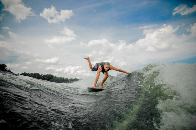 Young and athletic man wakesurfing on the board down the river against the sky