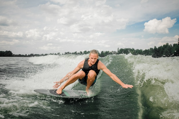 Young and athletic man wakesurfing on the board down the river