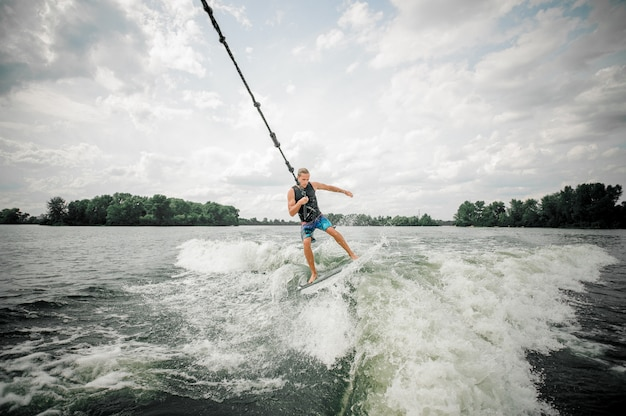 Young and athletic man wakesurfing on the board holding a cable