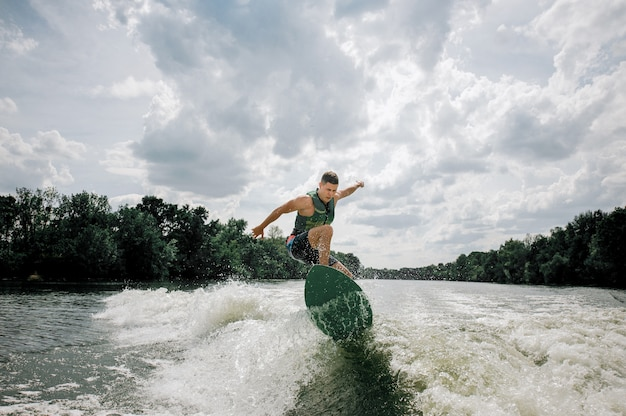 Young and athletic man wakesurfing on the board