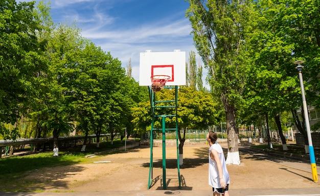 무성 한 녹색 공원에서 농구 코트에서 그물에 공으로 성공적인 샷을 보고 젊은 운동 남자