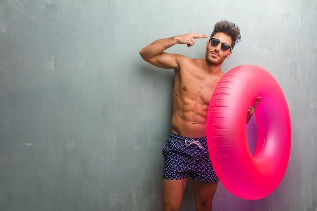 Молодой спортивный человек в купальнике на стене гранж, делая жест самоубийства, чувствуя грусть и испуг, формируя пистолет с пальцами