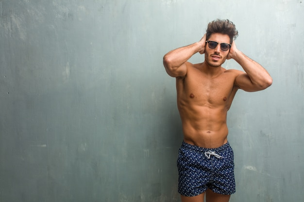 Young athletic man wearing a swimsuit against a grunge wall covering ears with hands, angry and tired of hearing some sound