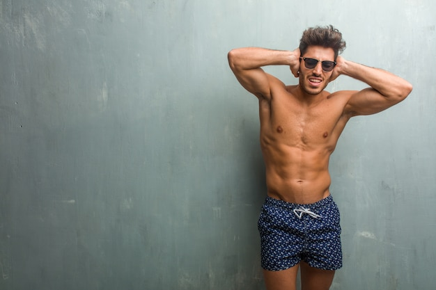 Young athletic man wearing a swimsuit against a grunge wall covering ears with hands