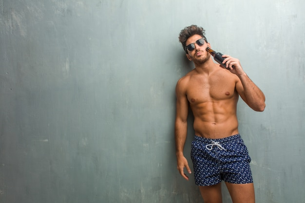 Young athletic man wearing a swimsuit against a grunge wall crazy and desperate, screaming out of control, funny lunatic expressing freedom and wild