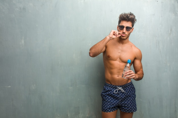 Young athletic man wearing a swimsuit against a grunge wall keeping a secret or asking for silence