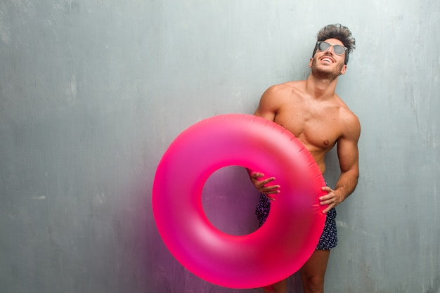 Young athletic man wearing a swimsuit against a grunge wall laughing and having fun, being relaxed and cheerful, feels confident and successful