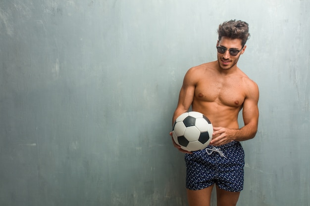 Young athletic man wearing a swimsuit against a grunge wall laughing and having fun