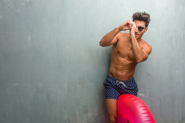 Young athletic man wearing a swimsuit against a grunge wall looking through a gap