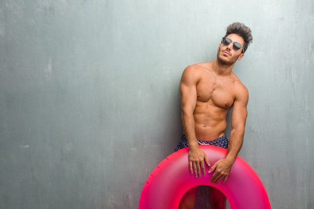 Young athletic man wearing a swimsuit against a grunge wall looking up
