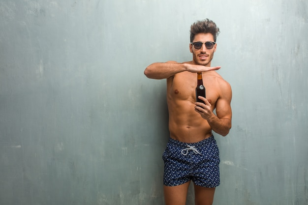 Young athletic man wearing a swimsuit against a grunge wall tired and bored, making a timeout gesture
