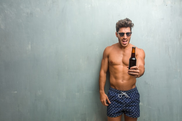 Young athletic man wearing a swimsuit against a grunge wall very angry and upset