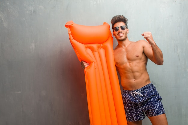 Young athletic man wearing a swimsuit against a grunge wall very happy and excited, raising arms, celebrating a victory or success, winning the lottery