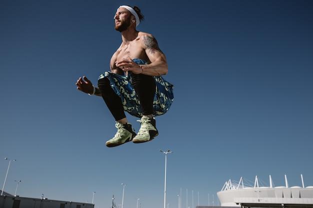 검은색 레깅스와 파란색 반바지를 입은 머리띠를 한 벌거벗은 몸통을 가진 젊은 운동선수가 화창한 화창한 날 푸른 하늘을 배경으로 높이 뛰어오르고 있습니다.