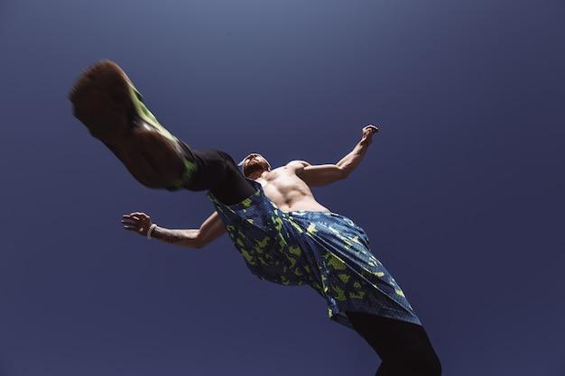 Молодой спортивный мужчина с обнаженным торсом и повязкой на голове, одетый в черные леггинсы и синие шорты, высоко прыгает на фоне голубого неба в теплый солнечный день.