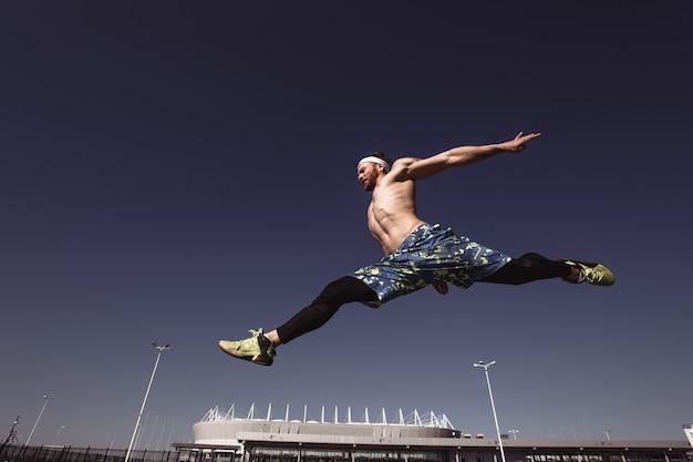 검은색 레깅스와 파란색 반바지를 입은 머리띠를 한 벌거벗은 몸통을 가진 젊은 운동선수가 화창한 날 경기장과 푸른 하늘 배경에서 높이 뛰어오르고 있습니다.