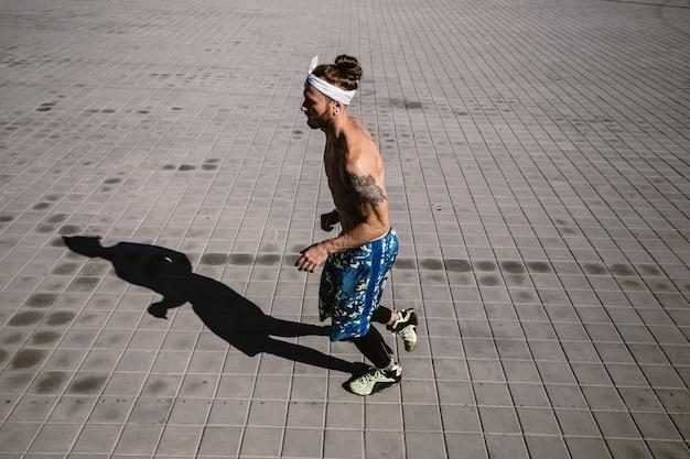 검은색 레깅스와 파란색 반바지를 입은 머리에 문신과 머리띠를 한 벌거벗은 몸통을 가진 젊은 운동선수는 따뜻하고 화창한 날 포장용 석판을 달리고 있습니다.