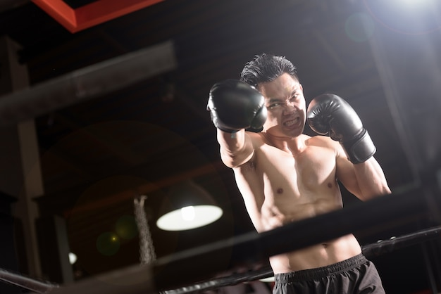 Young athletic man with boxing gloves on boxing ring