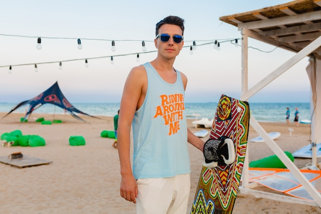 Young athletic man with kite surfing board posing on beach wearing sunglasses on summer vacation