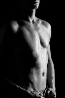 Young athletic man with naked torso in jeans standing over black background in photo studio