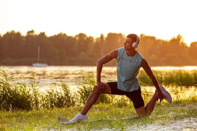운동하는 젊은 운동 남자, 야외 강변에서 훈련.