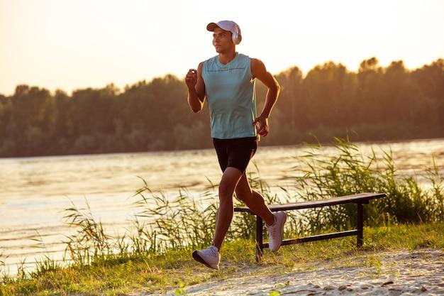 Giovane uomo atletico che si allena, si allena ascoltando musica in riva al fiume all'aperto.