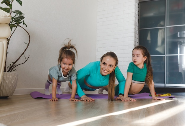 A young and athletic mother in a tracksuit is engaged in fitness at home with her daughters
