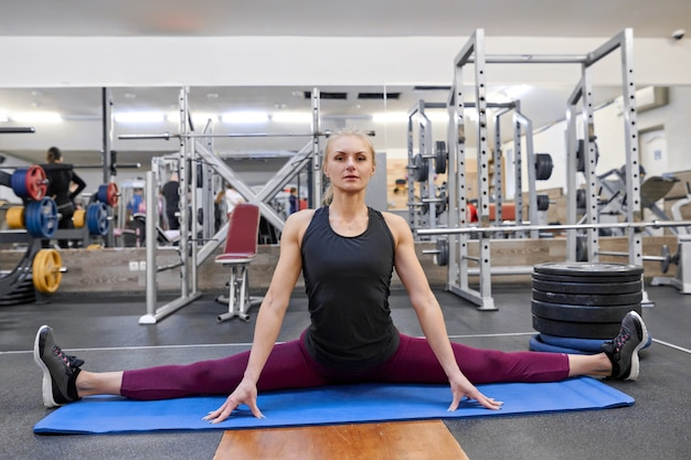 Young athletic muscular woman doing stretching workout in the gym