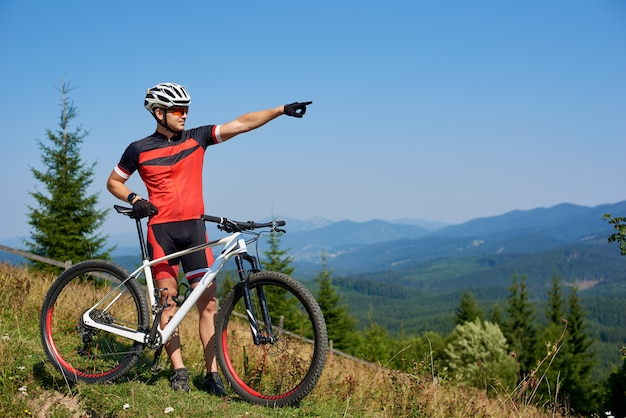 Young athletic professional biker standing with bicycle on top of hill