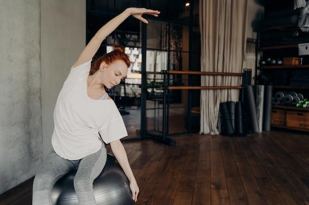 흰색 특대형 티셔츠를 입은 젊은 운동선수 빨간 머리 소녀는 큰 핏볼에 앉아 피트니스 스튜디오 장비의 배경에 대해 몸을 좌우로 구부립니다. 필라테스 운동 개념