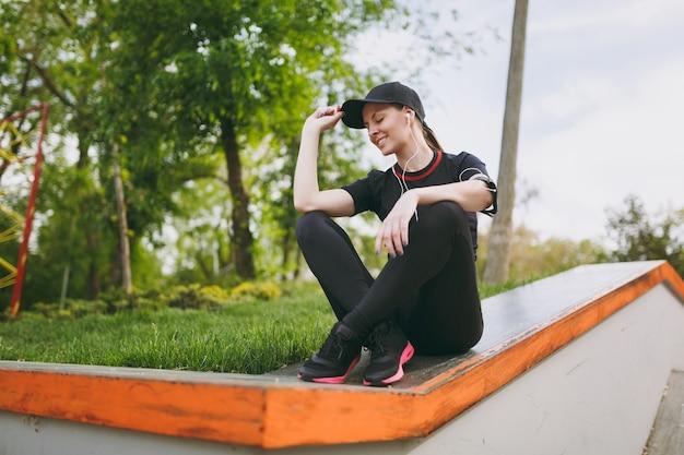 Giovane bella donna atletica rilassante in uniforme nera e berretto con le cuffie che ascolta la musica riposando e seduta prima o dopo la corsa, allenamento nel parco cittadino all'aperto