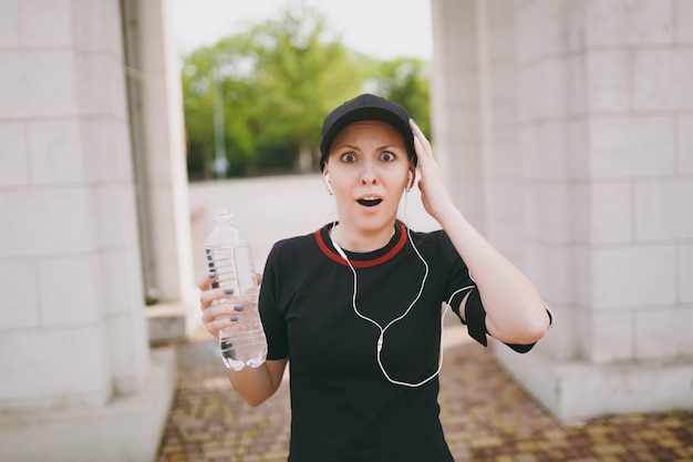 Young athletic shocked beautiful brunette woman in black uniform and cap with earphones holding bottle with water, listening to music spreading hands in city park outdoors