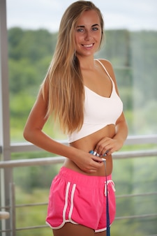 Young athletic slender woman measures the waist.