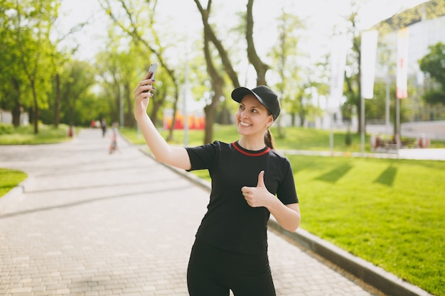 Young athletic smiling beautiful brunette girl in black uniform, cap doing selfie on mobile phone during training, showing thumb up, standing in city park outdoors
