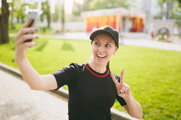 Young athletic smiling beautiful brunette girl in black uniform and cap doing selfie on mobile phone during training, showing victory sign, standing in city park outdoors