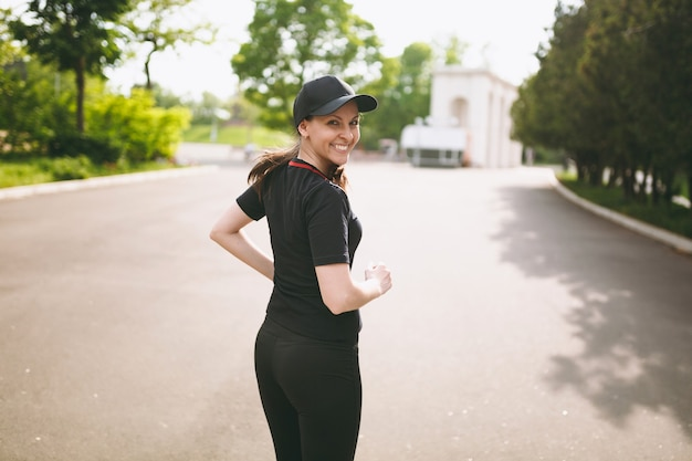 Young athletic smiling beautiful brunette girl in black uniform and cap training, doing sport exercises and running, looking back on path in city park outdoors