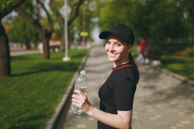 屋外の都市公園に立って走る前にトレーニング中に水で、黒い制服とキャップ保持ボトルで若い運動笑顔の美しいブルネットの少女