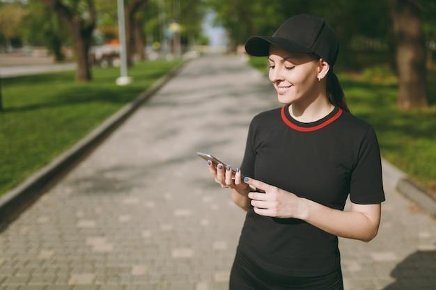 トレーニング中に携帯電話を使用して、スマートフォンを見て、屋外の都市公園に立っている黒い制服と帽子の若い運動笑顔の美しいブルネットの少女