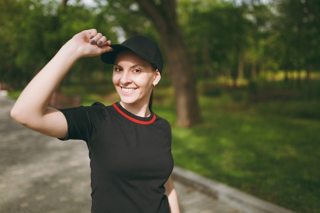 Young athletic smiling beautiful brunette woman in black uniform and cap standing, looking on camera keeping hand near cap on training on path in city park outdoors