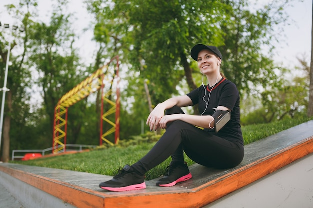 Young athletic smiling beautiful woman in black uniform and cap with headphones listening to music, resting and sitting before or after running, training in city park outdoors