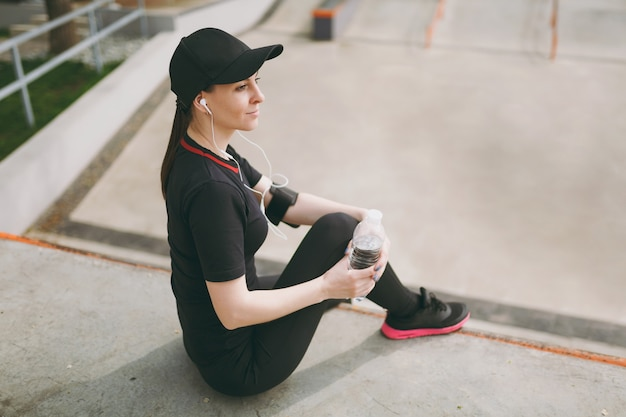 Young athletic smiling woman in black uniform, cap with headphones listening to music holding bottle with water sitting before or after running, training in city park outdoors